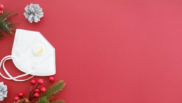Una mascarilla médica junto a las ramas de abeto con bolas navideñas. protección contra coronavirus en nochevieja y nochebuena. quédate en casa y no te enfermes