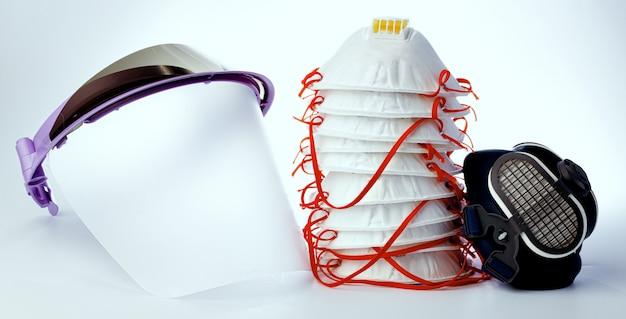 Mascarilla médica y máscaras de protección sobre fondo blanco.