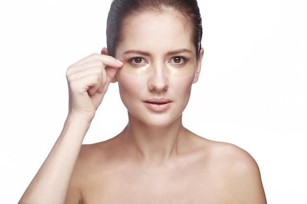 Mascarilla para la piel de los ojos. mujer con parches debajo de los ojos en la cara