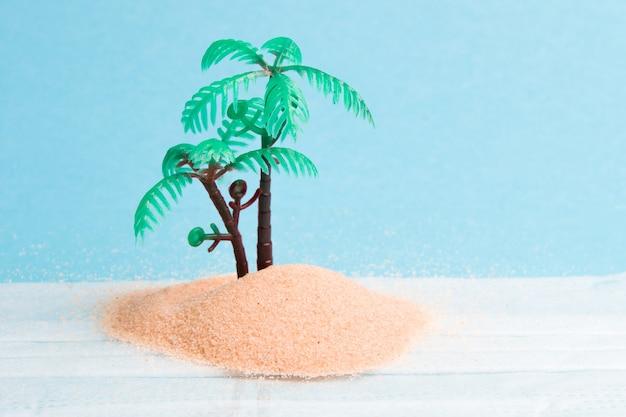 Mascarilla de plástico de palmera y arena sobre fondo azul.