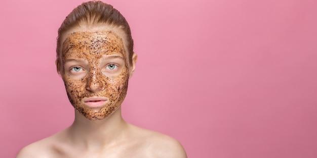 Mascarilla de posos de café exfoliante facial para la piel en el rostro de una hermosa mujer joven