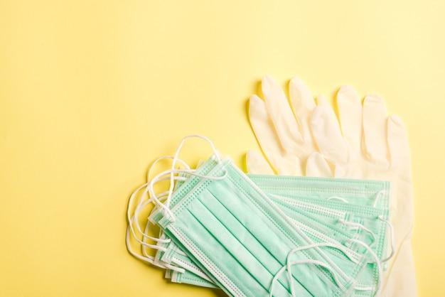 Mascarilla protectora médica y guantes de goma, foto de estudio aislado sobre fondo amarillo. seguridad asistencia sanitaria médica prevenir coronavirus o covid-19