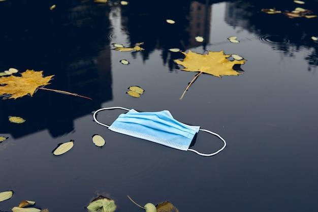 Mascarilla protectora médica en el suelo de la calle. mascarilla desechable usada perdida en el pavimento. residuos durante covid-19.