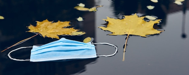 Mascarilla protectora médica en el suelo de la calle. mascarilla desechable usada perdida en el pavimento