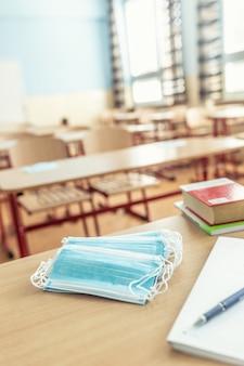 Mascarilla en un pupitre y profesores en un aula de la escuela.