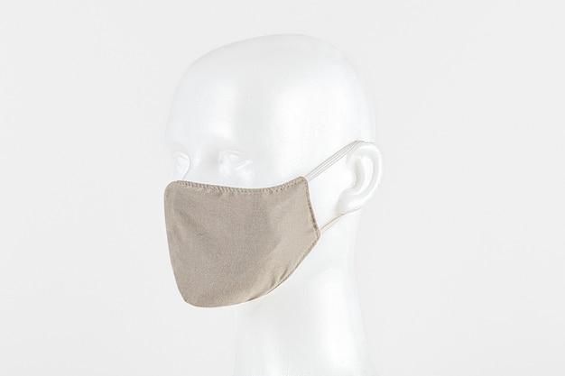 Mascarilla de tela beige sobre una cabeza falsa