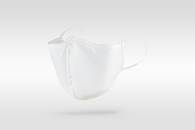 Mascarilla de tela blanca sobre blanco roto
