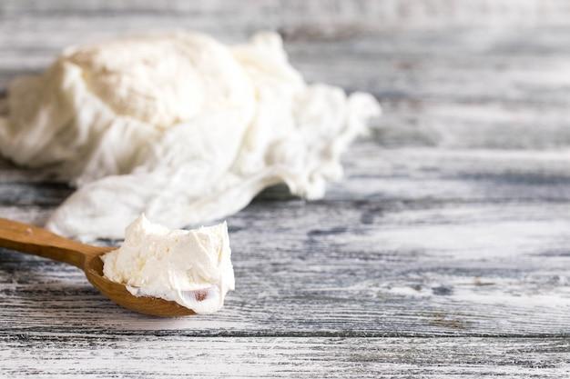 Mascarpone casero fresco. queso mascarpone tradicional en cuchara de madera