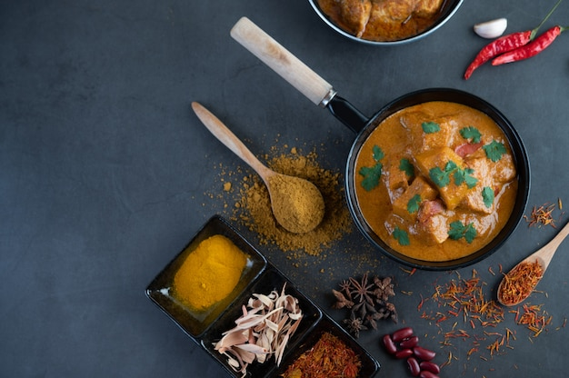 Massaman curry en una sartén con especias en el piso de cemento