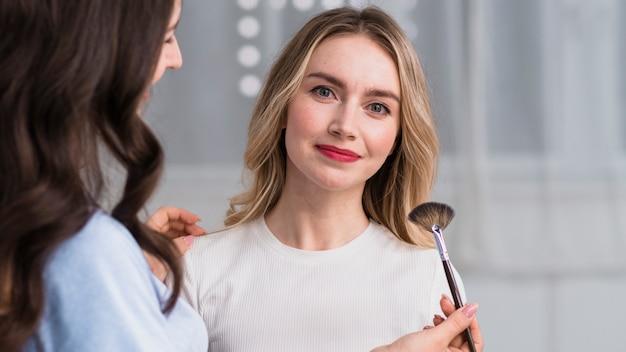 Master aplicando maquillaje a mujer rubia sonriente