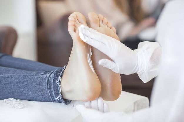 Master haciendo masaje de pies, desinfección antes del procedimiento de pedicura.