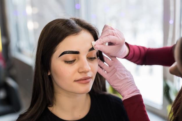 Master haciendo los pasos finales en el procedimiento de maquillaje en el salón