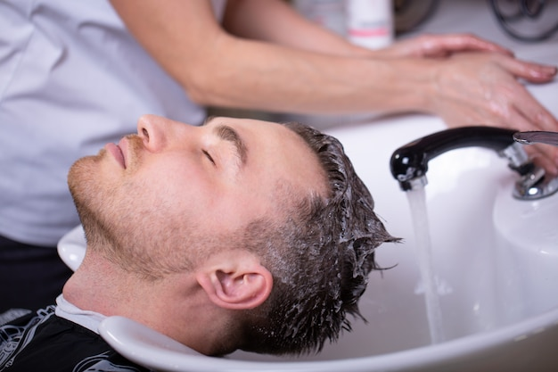 Master lava la cabeza de un cliente en la peluquería, el peluquero hace el peinado para un joven.