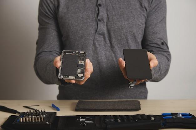 Master sostiene el cuerpo del teléfono inteligente y la nueva pantalla de reemplazo sobre el kit de herramientas para su reparación en la mesa blanca