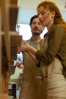 Masterclass de alfarería. sonriente mujer de jengibre escuchando atentamente al maestro de cabello oscuro mientras revisa ejemplos de arte en arcilla