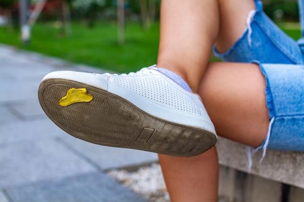 Masticar chicle pegado a los zapatos durante un paseo por la ciudad
