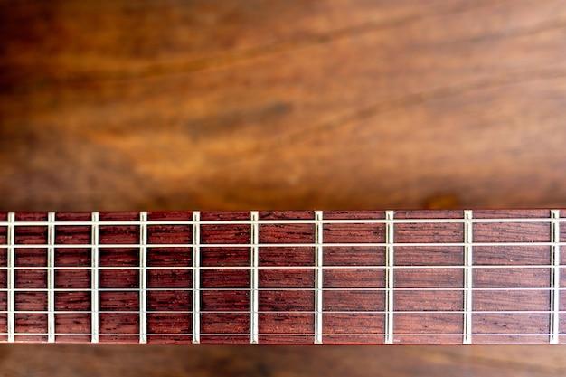 Mástil de una guitarra eléctrica sobre suelo de madera.