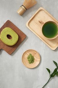 Matcha de té verde en una taza de madera con pastel alemán en la alfombra marrón de cerca