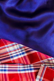 Material de algodón tartán sobre tejido azul liso.