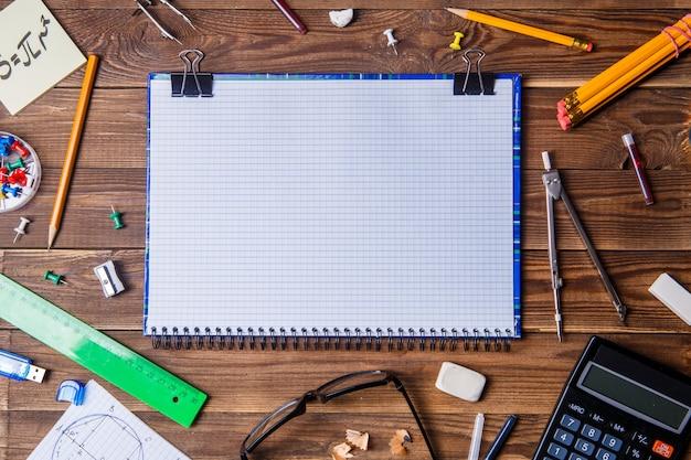 Material del alumno con cuaderno para texto en la mesa de madera.