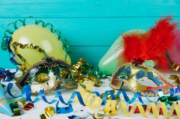 Material de decoración de fiesta con máscara de carnaval de disfraces y globos.