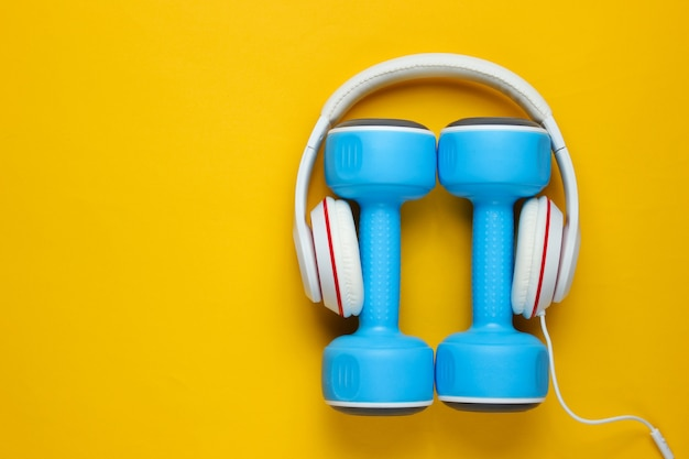 Material deportivo sobre fondo amarillo. estilo de vida deportivo. mancuernas, auriculares. concepto de fitness. vista superior, minimalismo, endecha plana.