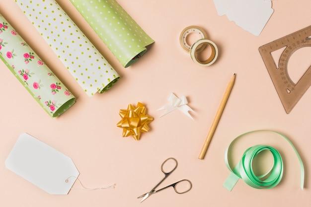 Material de embalaje de regalo dispuesto sobre papel tapiz de durazno