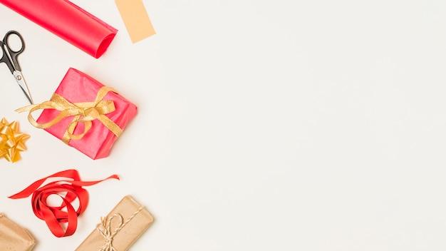 Material para envolver regalos y regalos dispuestos al costado del fondo.