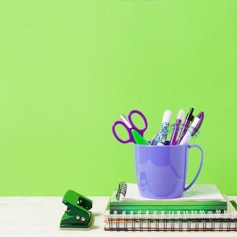 Material escolar con fondo verde.