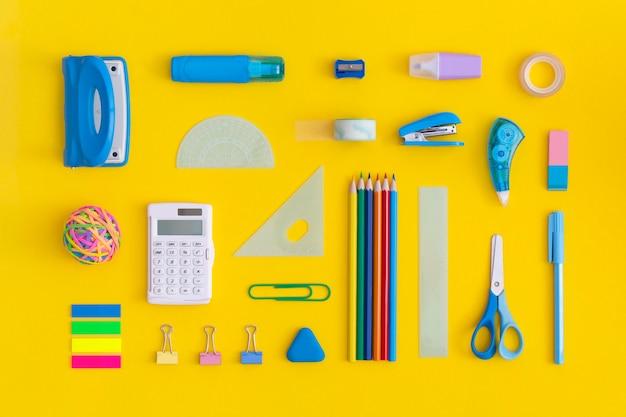 Material escolar sobre un fondo amarillo. vista superior. endecha plana. concepto de regreso a la escuela.