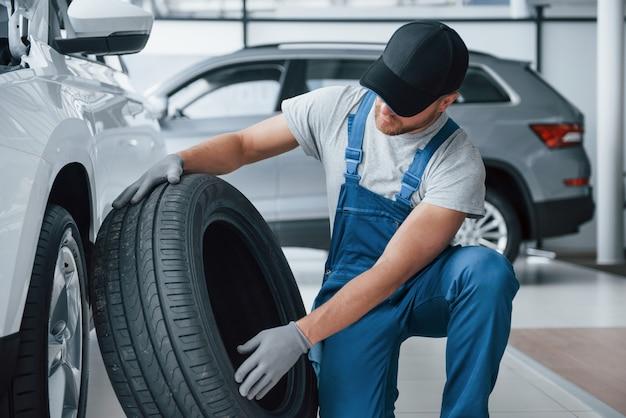 Material fresco. mecánico sosteniendo un neumático en el taller de reparación. reemplazo de neumáticos de invierno y verano.