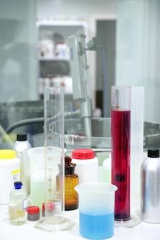 Material de laboratorio, cilindro de vidrio, líquidos coloridos.