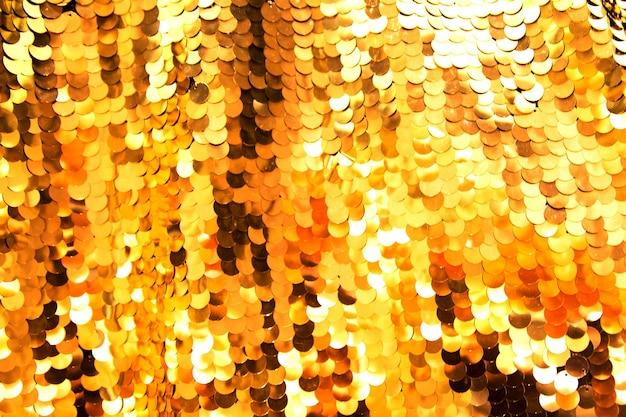 Material de lentejuelas doradas brillantes como fondo de vacaciones. concepto festivo. movimiento borroso.