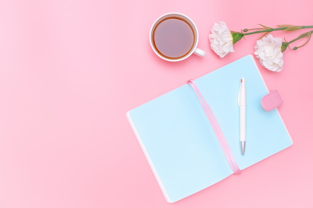 Material de oficina del escritorio del área de trabajo, té caliente y flor blanca sobre fondo rosa pastel