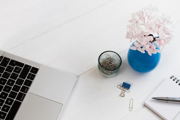 Material de oficina y flores en maceta sobre mesa.