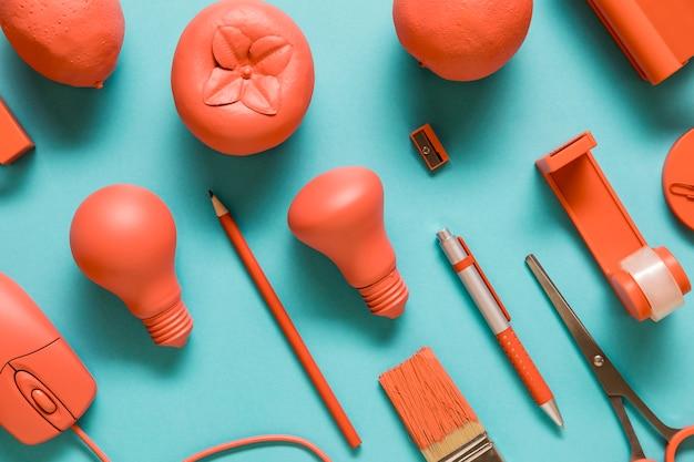 Material de oficina y frutas de color rosa.