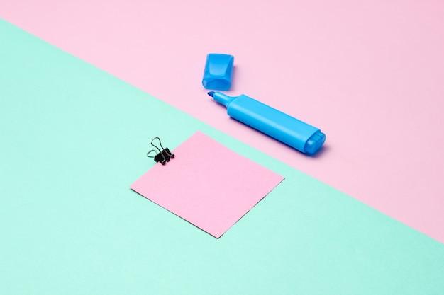 Material de oficina de papelería. clip de papel, rotulador, papel de nota sobre fondo rosa azul pastel