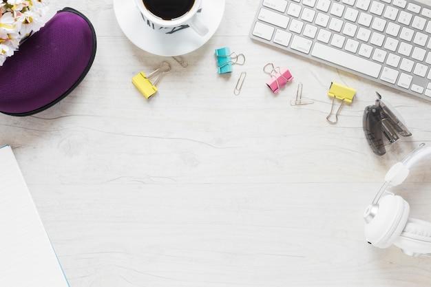 Material de oficina; taza de café; auriculares y teclado en el escritorio blanco