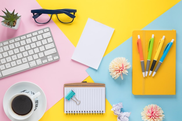 Material de oficina; taza de café y teclado en lugar de trabajo colorido