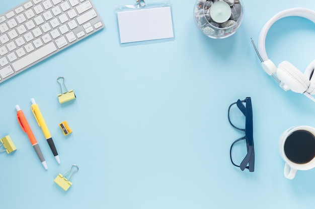 Material de oficina; teclado; taza de café; tarjeta; los anteojos; vela y auriculares sobre fondo azul