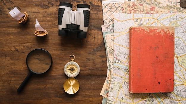 Material de viaje cerca de libros y mapas