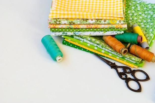Materiales a mano cosiendo en blanco