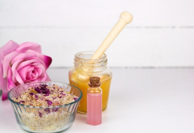 Matorral de sol de mar, botella de aceite esencial de rosa y espacio de copia de tarro de miel