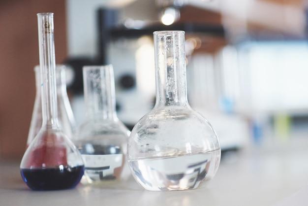 Matraz con soporte de corcho de laboratorio líquido rosa púrpura azul sobre la mesa en la prueba de fluido de laboratorio de prueba.