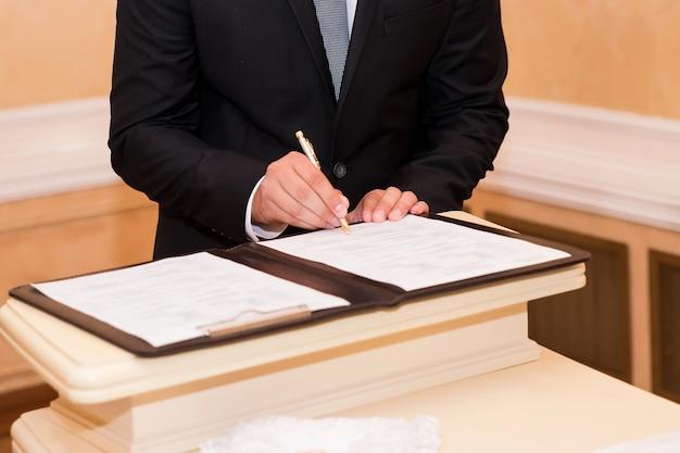 Matrimonio firmando registro, con pluma y documento oficial novios