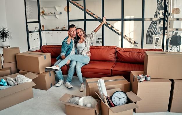 Matrimonio joven sentado en un sofá abrazos en la sala de estar en casa. feliz esposo y esposa se divierten, esperan un nuevo hogar. mudanza, compra de una casa, concepto de apartamento.