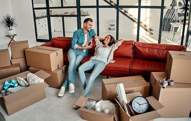 Matrimonio joven sentado en el sofá de la sala de estar en casa. feliz esposo y esposa se divierten, esperan un nuevo hogar. mover y reubicar el nuevo concepto de hogar.