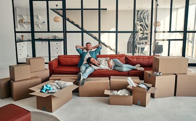 Matrimonio joven sentado en el sofá de la sala de estar en casa. feliz esposo y esposa se divierten, esperan un nuevo hogar. mudanza, compra de una casa, concepto de apartamento.