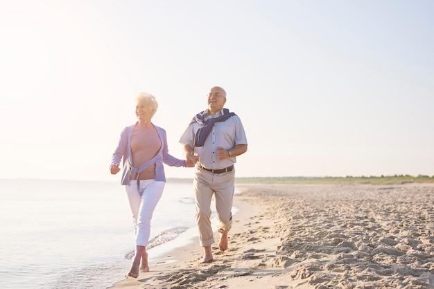 Mayores vitales en la playa. pareja senior en la playa, la jubilación y el concepto de vacaciones de verano