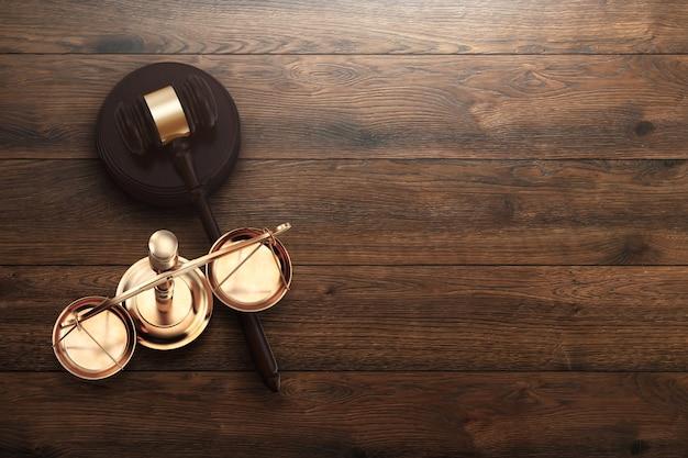 Mazo y balanza del juez sobre fondo de madera.